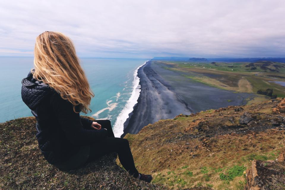 A woman overlooks a black sand beach on a cold day