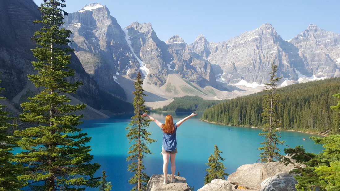 Picture of a girl standing on a rock with outstretched arms overlooking a lake and mountains in the background