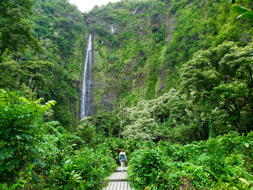 Picture of a girl hiking through a tropical forest towards a water fall