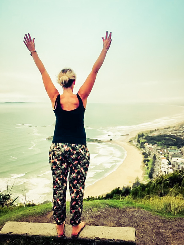 Picture of a woman standing up on a hill overlooking a city at the sea with her hands raised up in the air