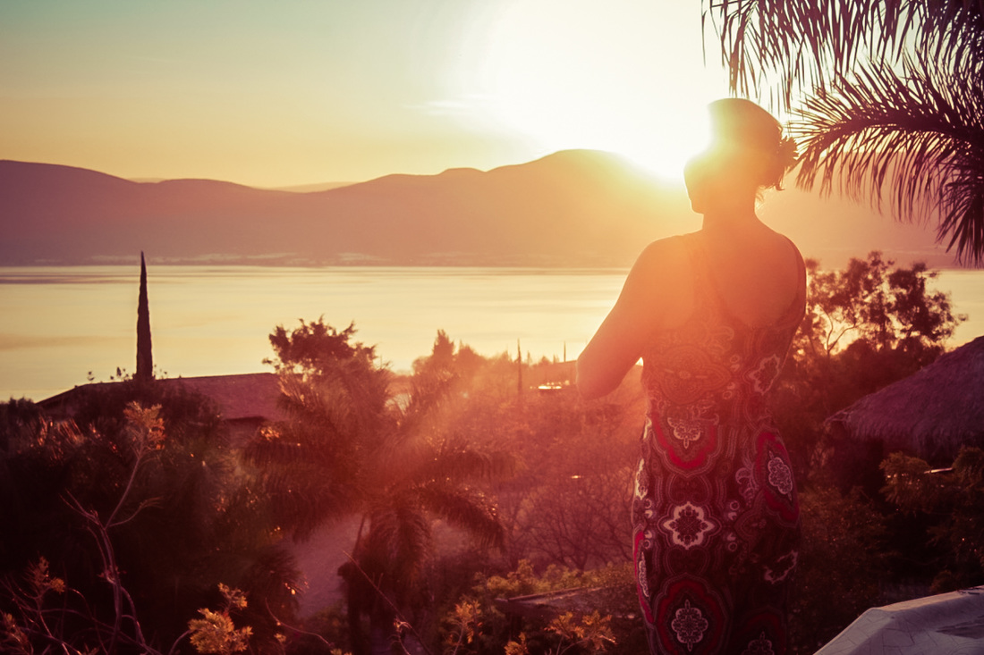 Picture of a woman overlooking the sea and mountains in Mexico at sunset