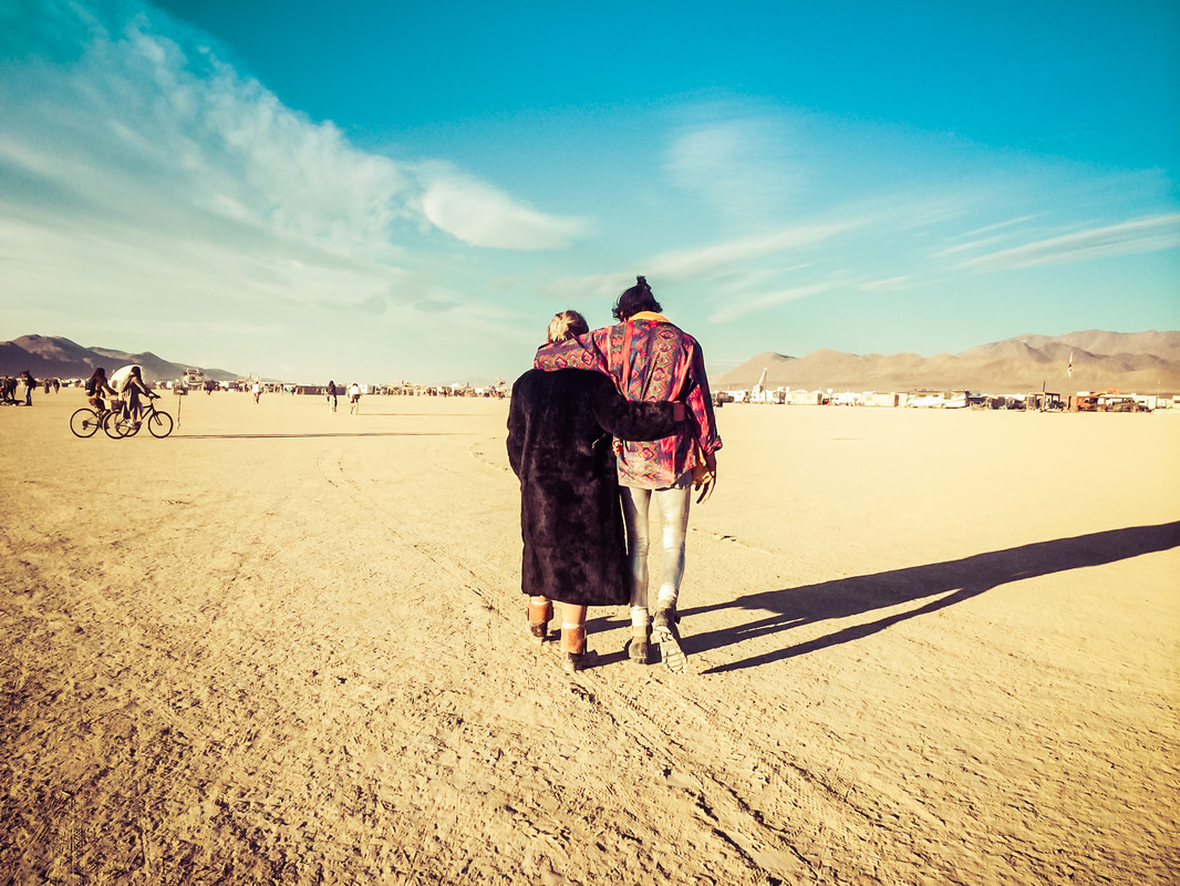 Picture of two people walking through the desert at Burning Man