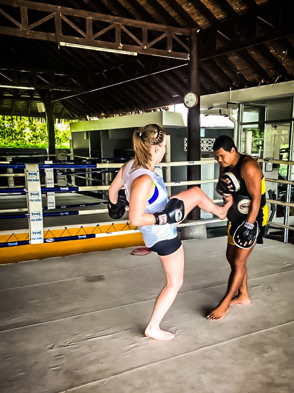 Picture of a woman and man in a boxing ring practicing kicking in Thailand