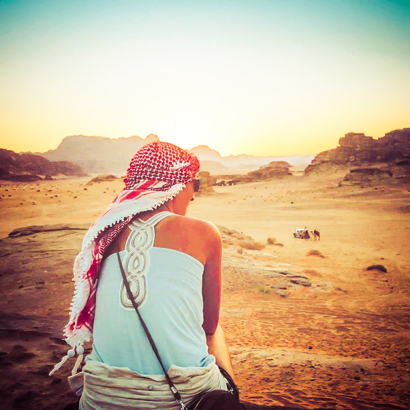 Picture of a woman with a headscarf sitting on a hill overlooking the desert in Turkey