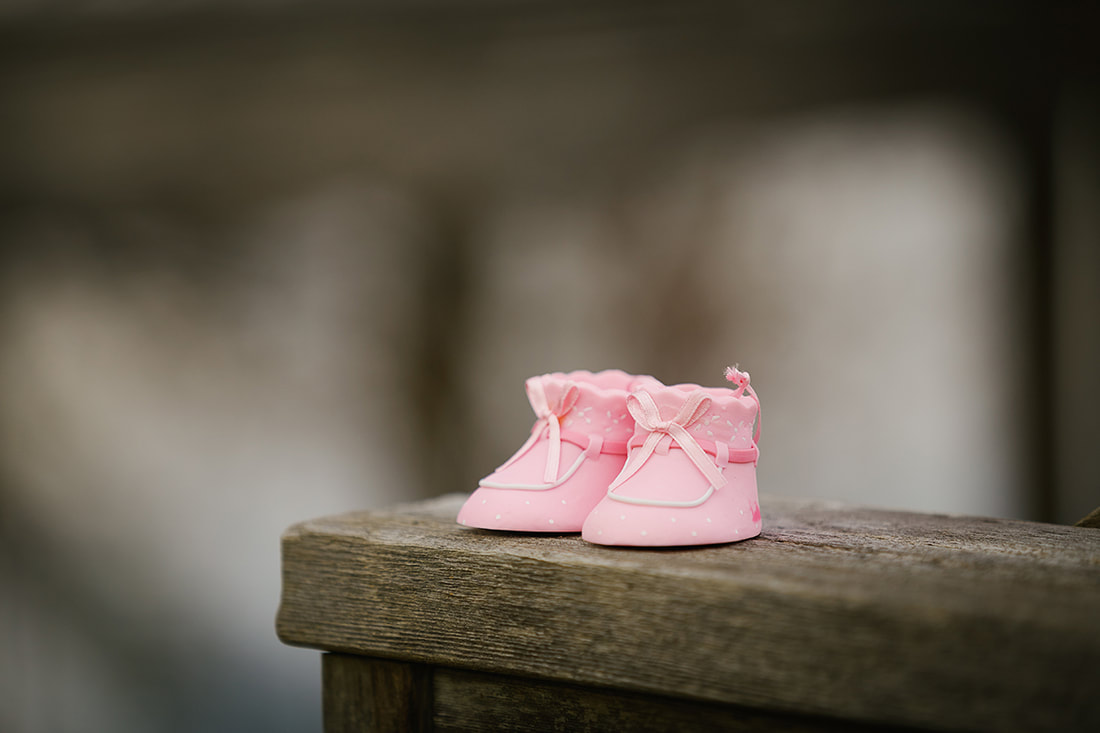 Pink baby shoes on a bench