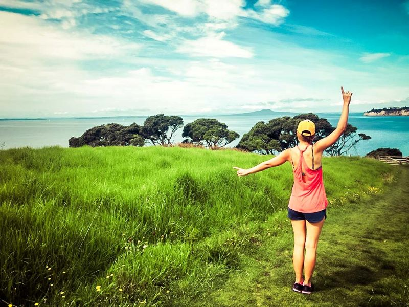 Picture of a woman standing on a grassy hill overlooking the sea with outstretched arms in New Zealand