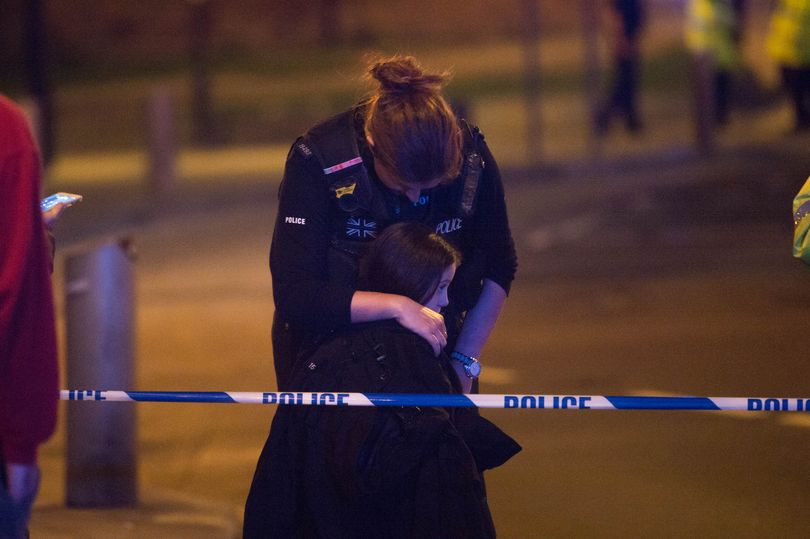 Police woman hugs little girl after shooting