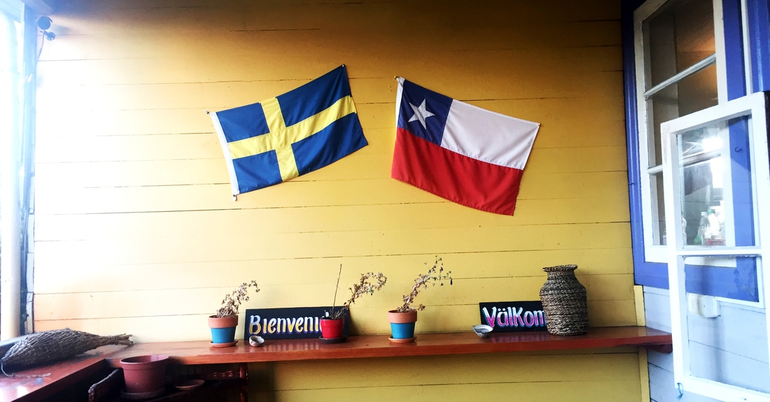 Picture of two flags on a wooden house wall