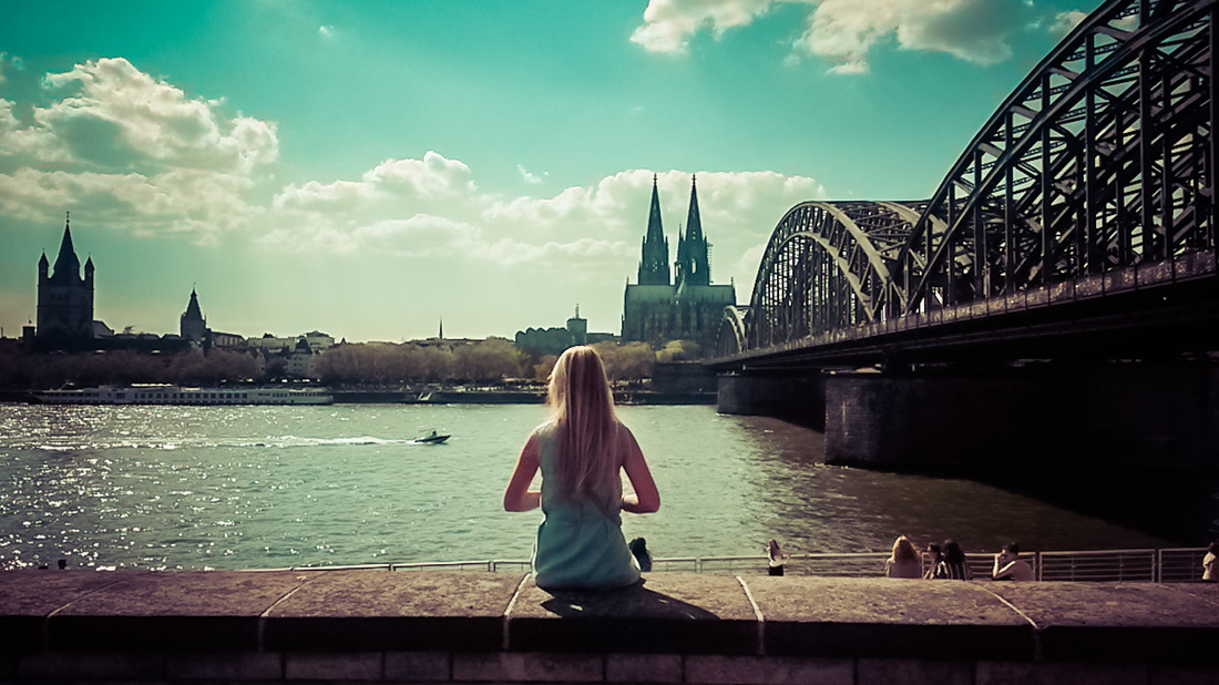 A woman overlooks the iconic Cologne cityscape view in Germany