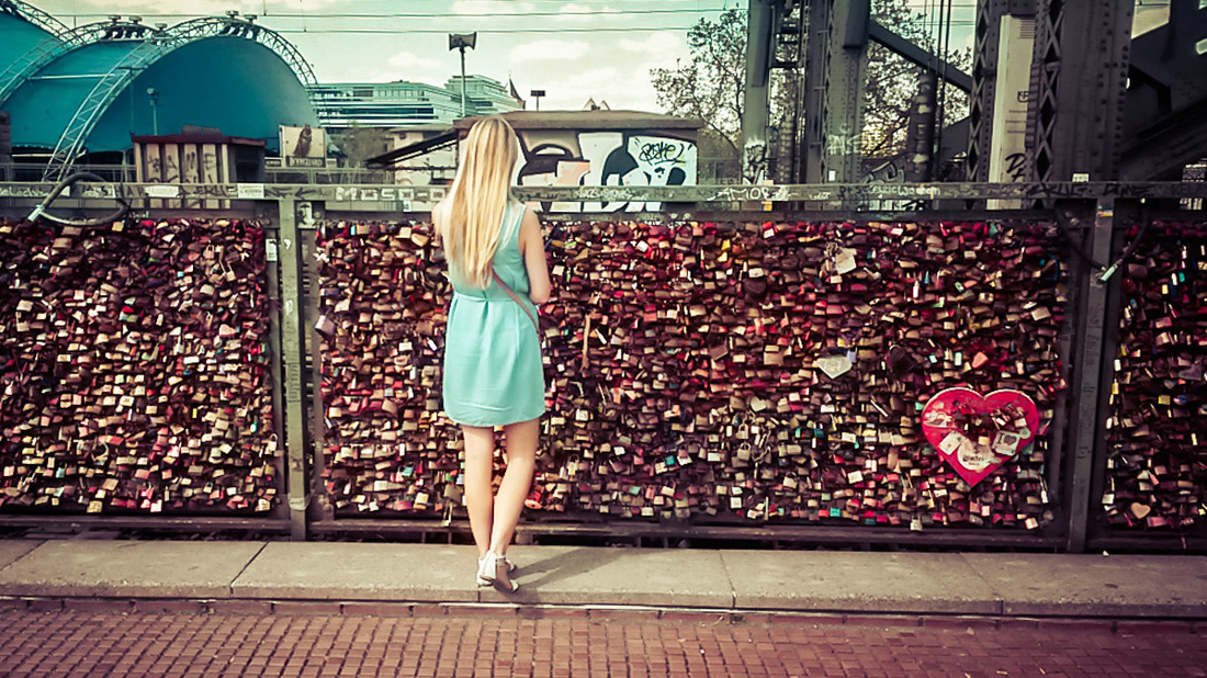 A woman stands at love lock bridge in Cologne, Germany