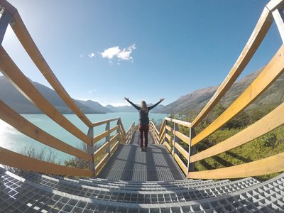 Woman stands on a bridge with Patagonian views in south Argentina