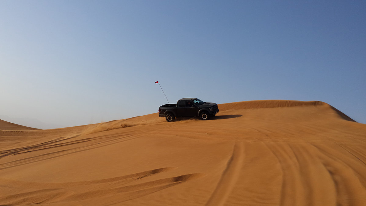 Picture of a black jeep driving over a sand dune in the Dubai desert