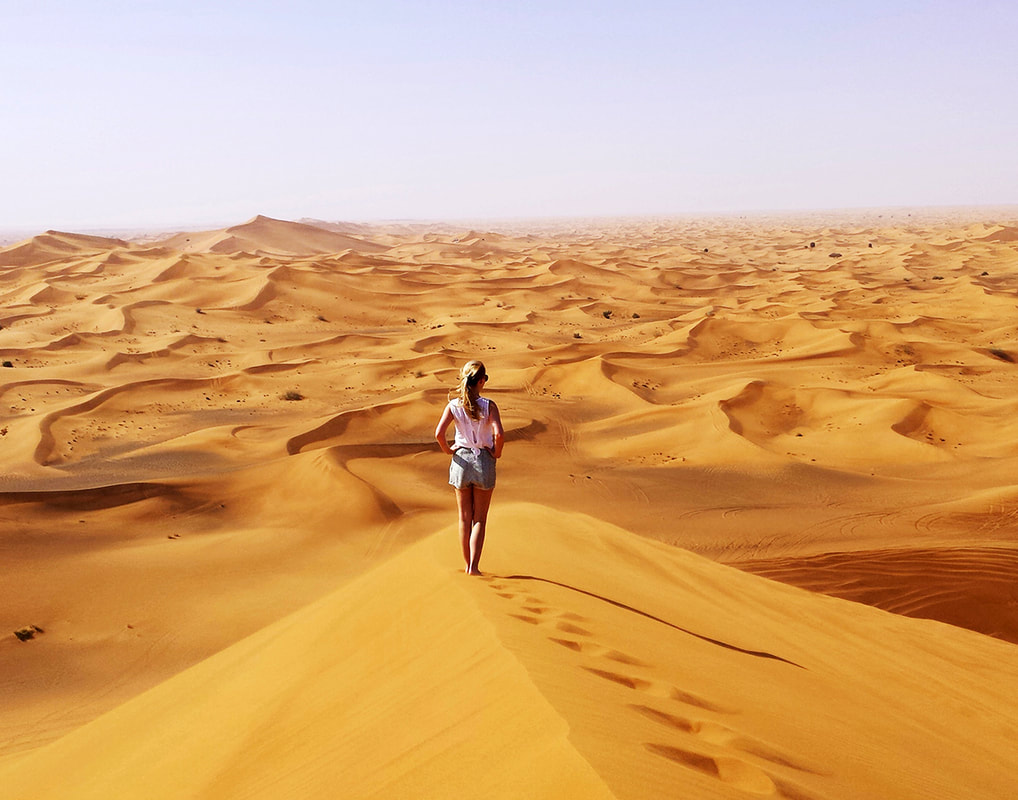Picture of a woman standing on a sand dune in the middle of the Dubai desert