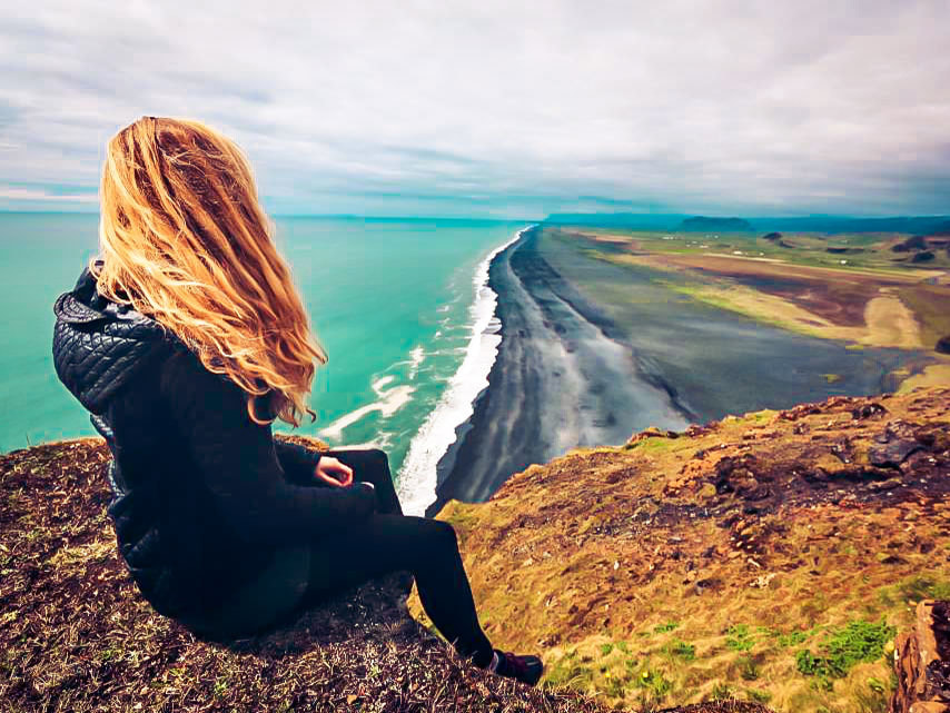 Picture of a woman sitting on a hill overlooking the beach and ocean in New Zealand