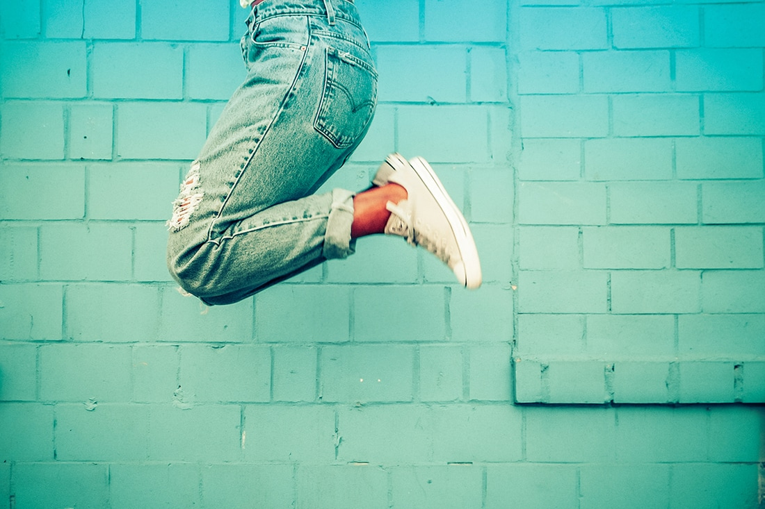 Woman jumping next to a blue brick wall