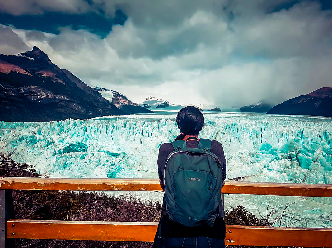 A woman standing in front of the Perito Moreno glacier in Argentina looking at the glacier ice and the mountains in the background