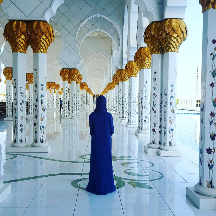 Picture of a woman standing inside of the Sheikh Zayed Mosque in Abu Dhabi wearing a traditional long blue robe