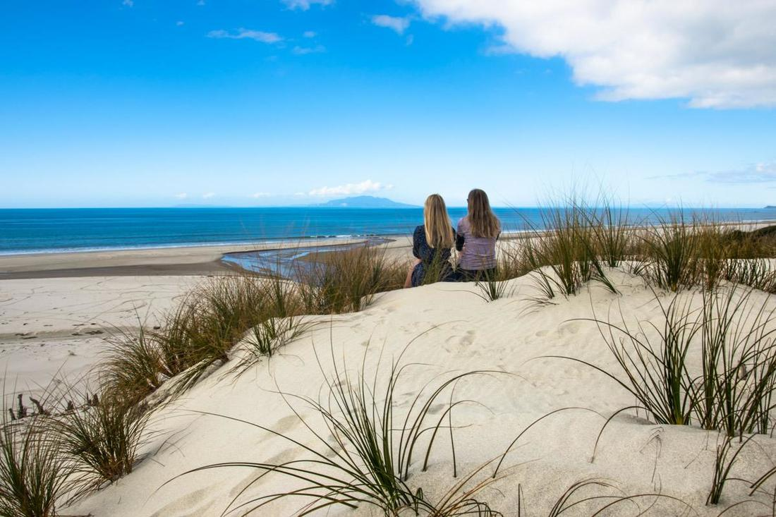 Two friends sit on a New Zealand beach