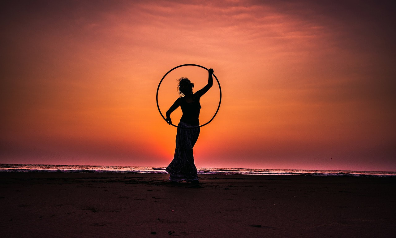 Girl with a hula hoop by the beach