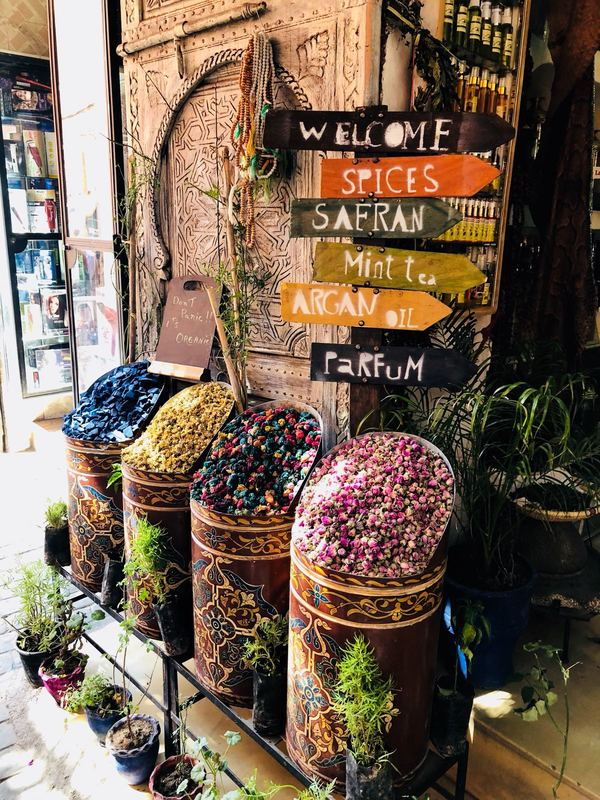 Colourful large tins and baskets with traditional Moroccan spices, herbs and flowers outside a market stall in Marrakesh, Morocco