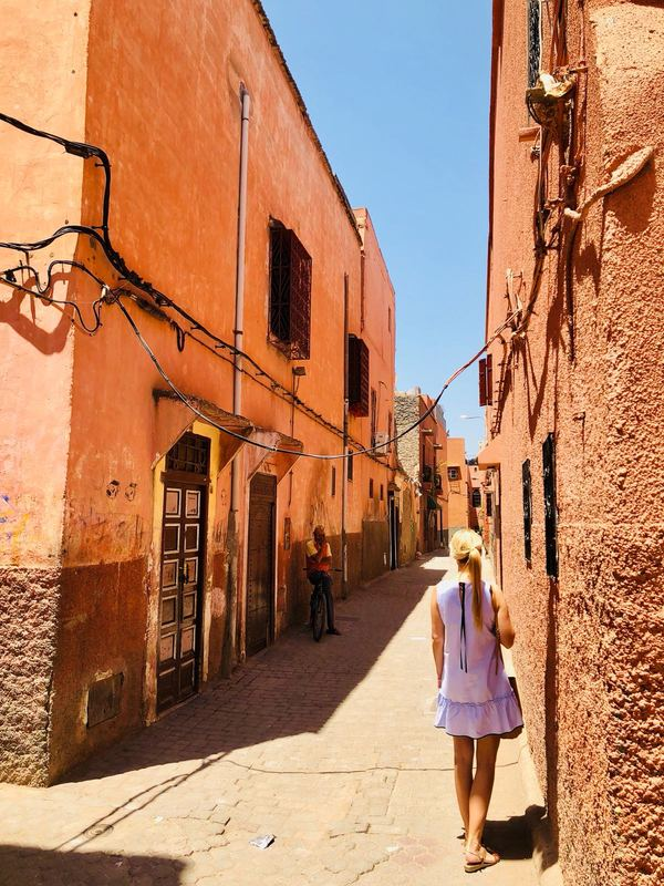 Woman standing in one of Marrakesh's alleyways facing away from the camera. She is surrounded by houses and walls in the typical Moroccan apricot colour