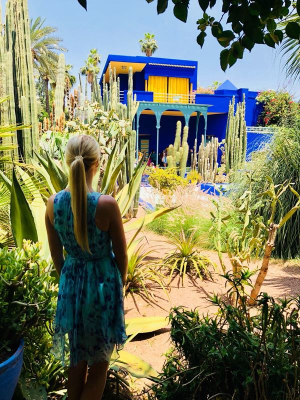 Woman standing in the Majorelle Gardens in Marrakesh, Morocco marveling at the famous blue and yellow villa designed by the French artist Jacques Majorelle