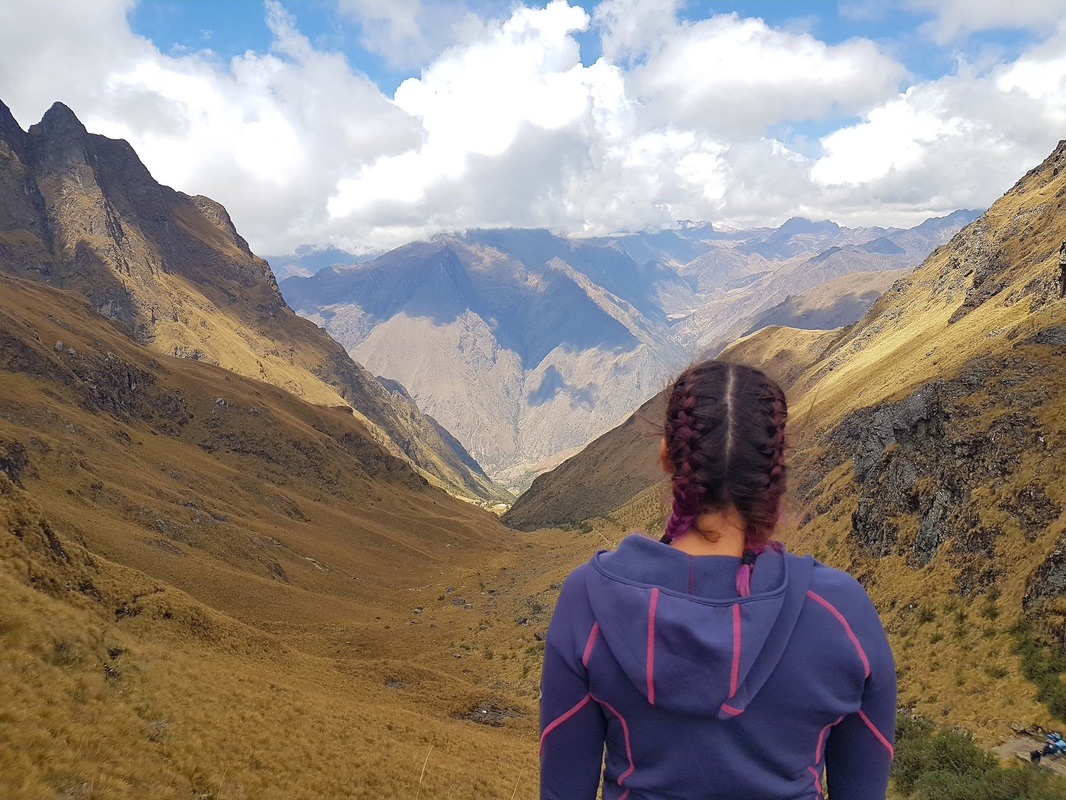 A woman admires the vast beauty of the Inca Trail