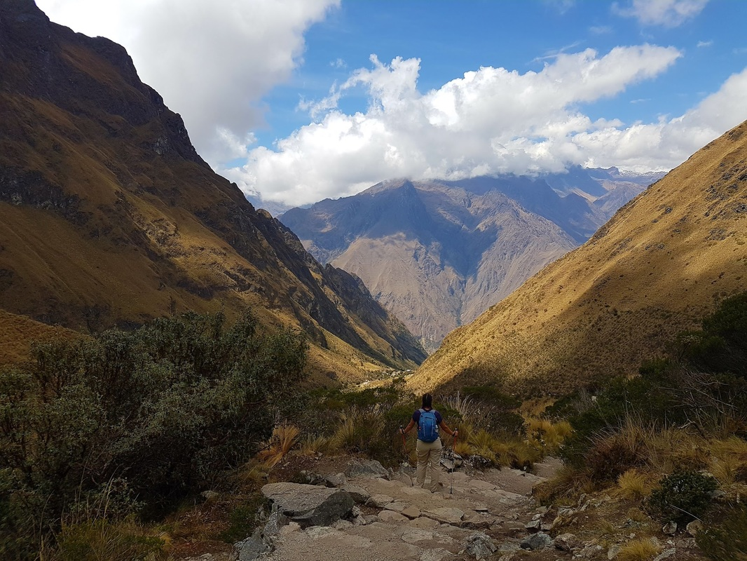 Hiking woman looks small against the backdrop of a vast mountainscape on the Inca Trail