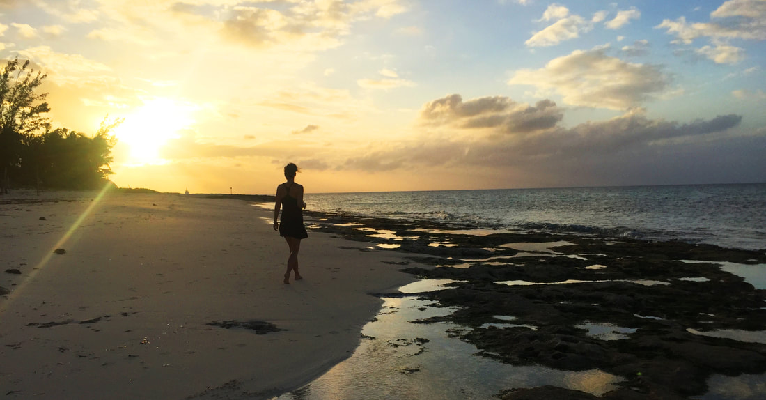 Woman walks along a Bahamian beach at sunset