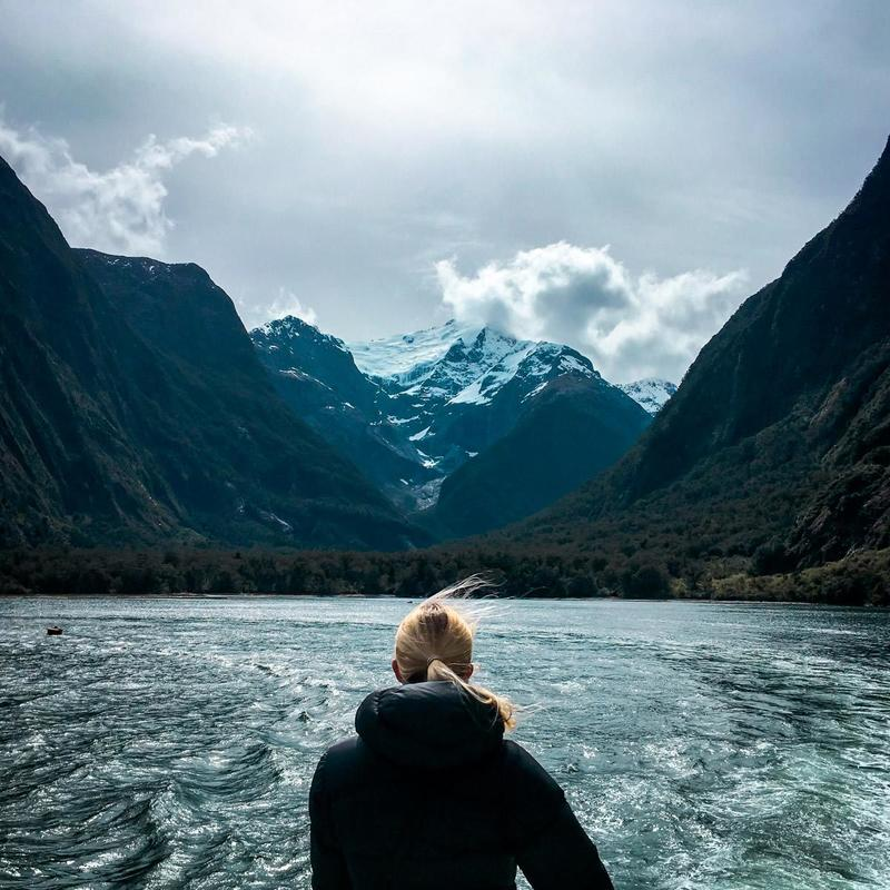 Woman overlooks Milford Sound in New Zealand