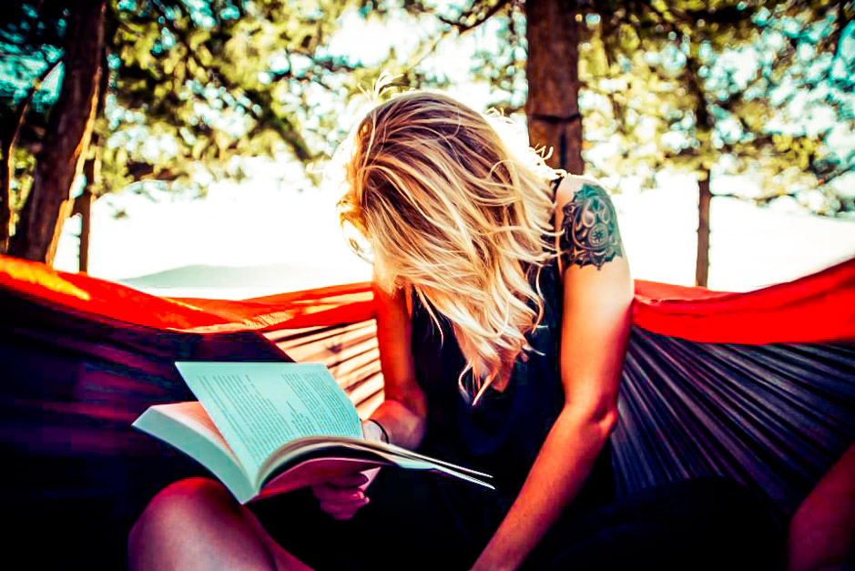 Woman with her nose buried in a book while camping