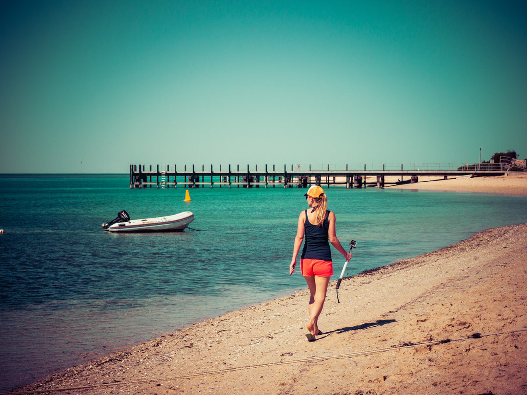 Woman walks along the beach at Monkey Mia, Western Australia