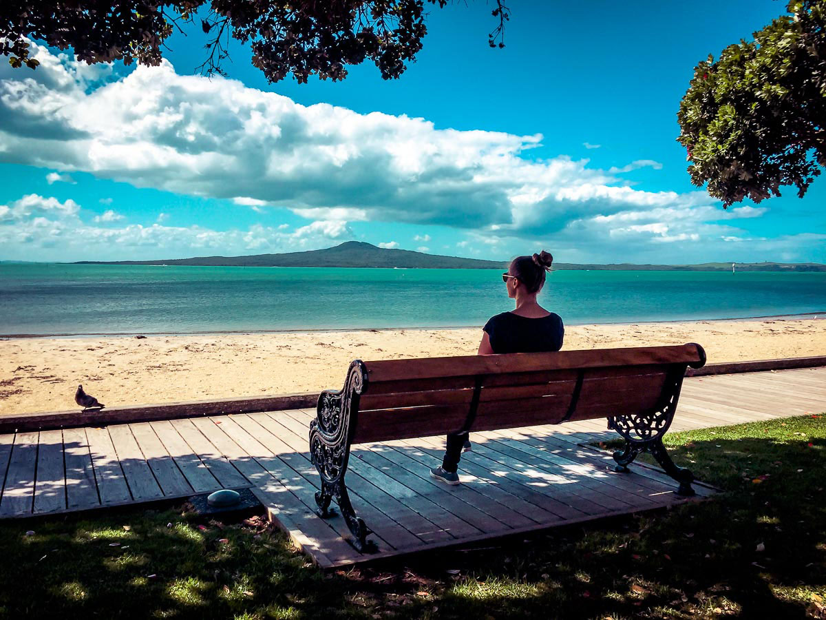 Woman overlooking Rangitoto island across the sea in Auckland, New Zealand