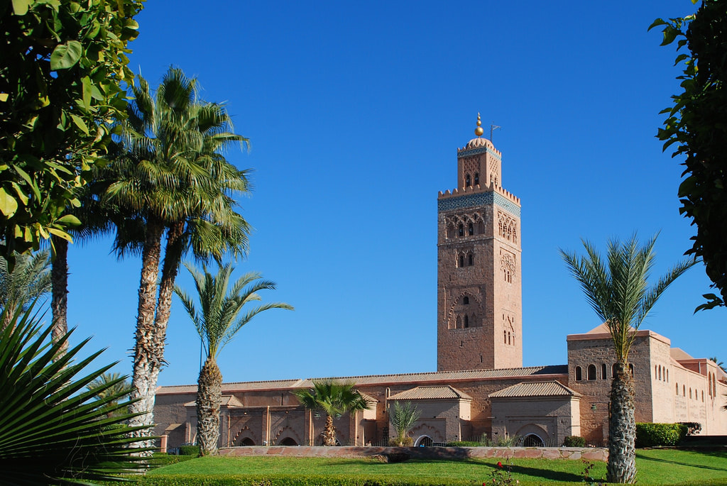 The Koutoubia Mosque and its garden in Marrakesh, Morocco on a bright and sunny day with blue skies surrounded  by palm trees