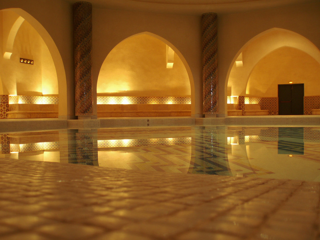Inside a traditional hammam in Marrakesh, dimmed light and a pool to relax in. The room has high ceilings and beautiful tiles decorate the walls