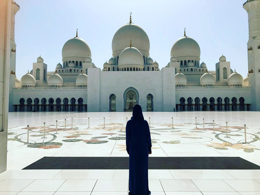 Picture of a woman standing in front of the Sheikh Zayed Mosque in Abu Dhabi wearing a traditional long blue robe