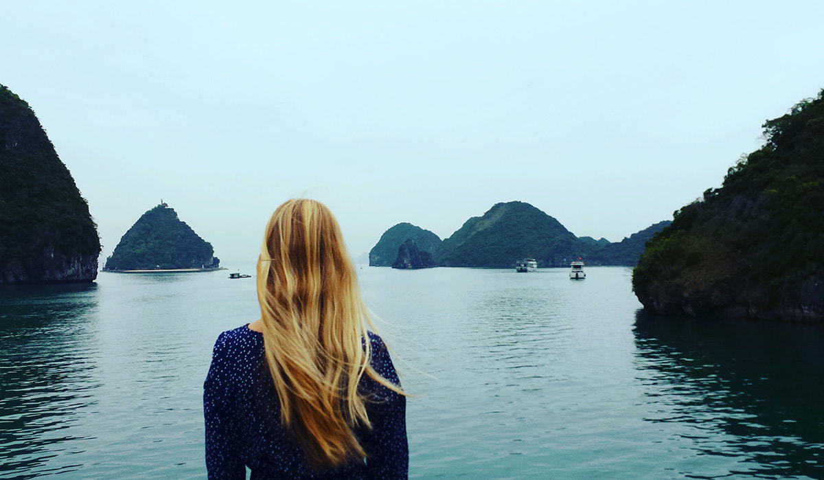 A woman looking out at Halong Bay on a moody day in Vietnam