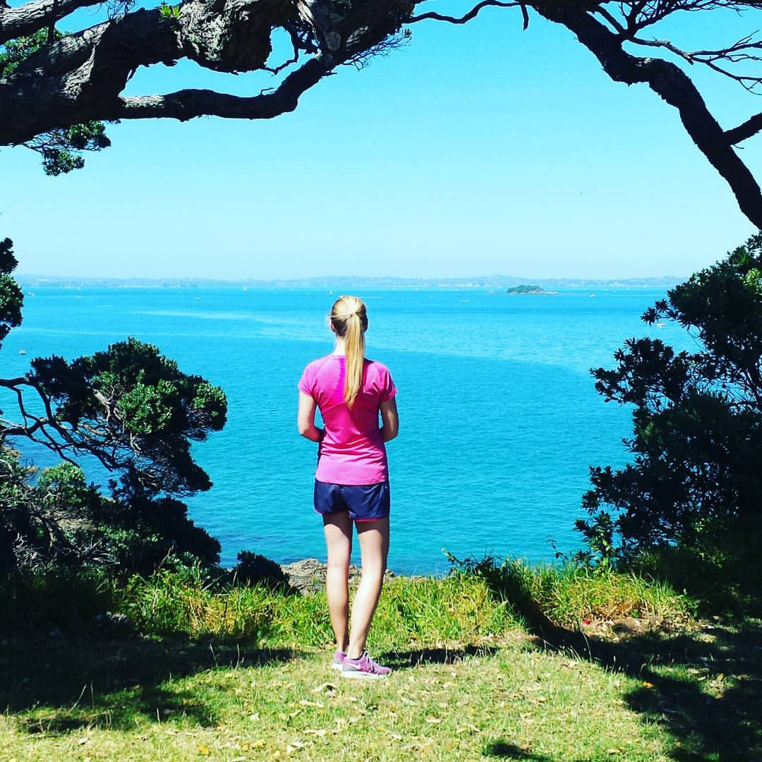 Woman overlooks brightly coloured summer seascape of New Zealand