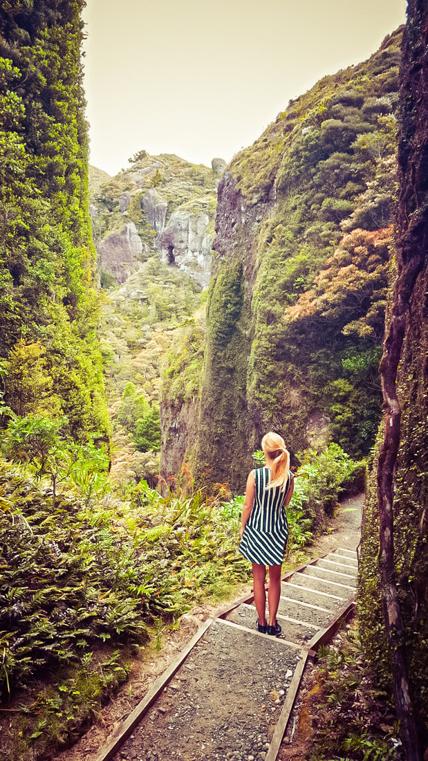 Picture of a woman standing in between mountains in a canyon on Great Barrier island in New Zealand.