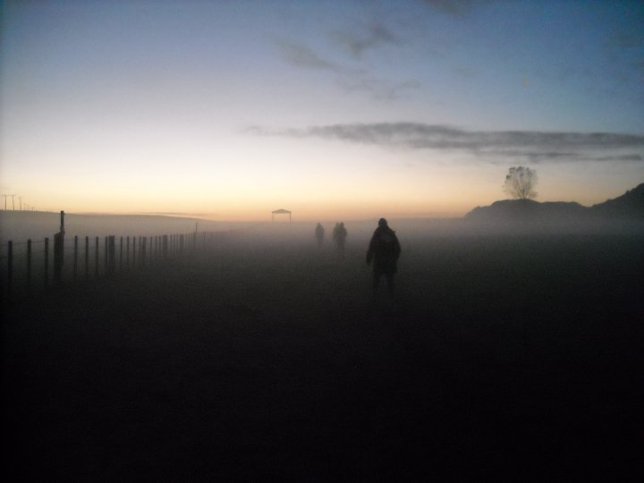 Picture of a woman walking through fog at sunrise