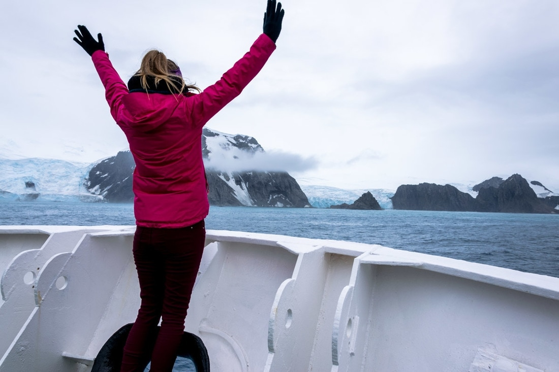 Woman stands triumphantly on bow of ship overlooking Antarctica