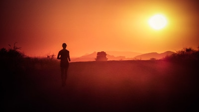 A silhouette of a woman running while the African sun begins to set