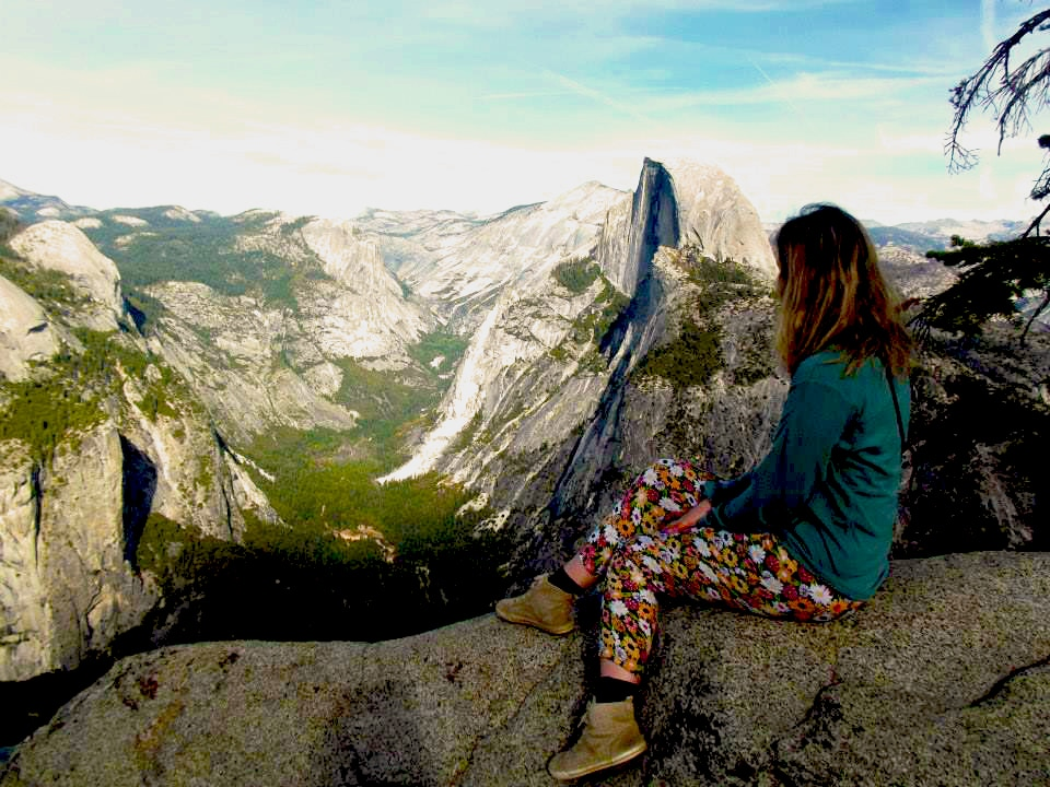 Hiking woman rests to overlook summer mountainscape
