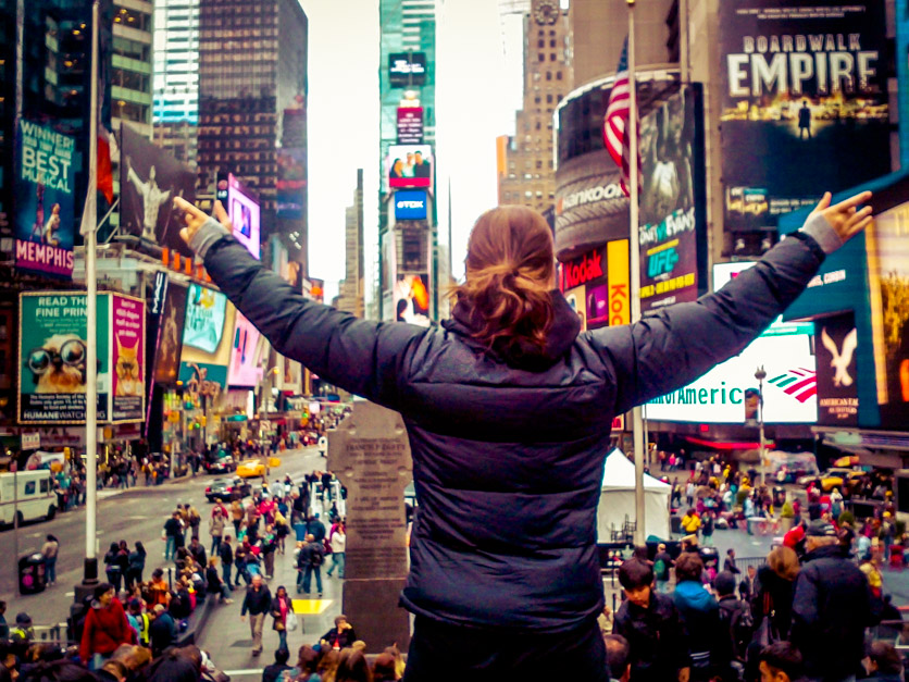 Picture of woman standing on Times Square in New York with her hands up in the air
