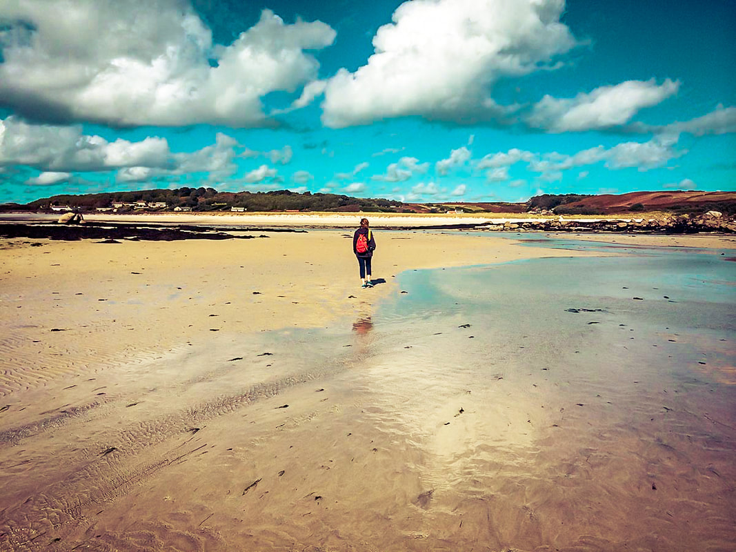 Woman walking along the St Martin's flats at low tide