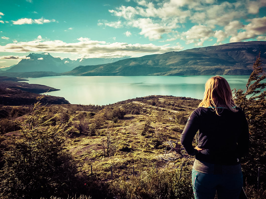 Picture of a woman overlooking a lake and mountains - Torres del Paine in Patagonia