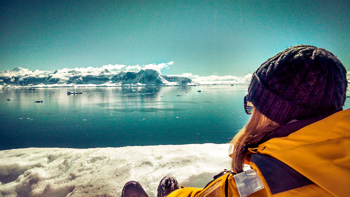 Woman overlooking the sea and icebergs in Antarctica