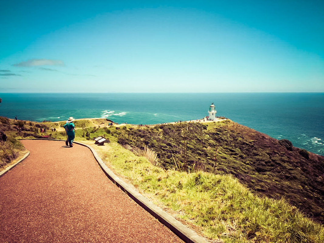 Picture of a woman overlooking the top of Cape Reinga and a lighthouse in New Zealand