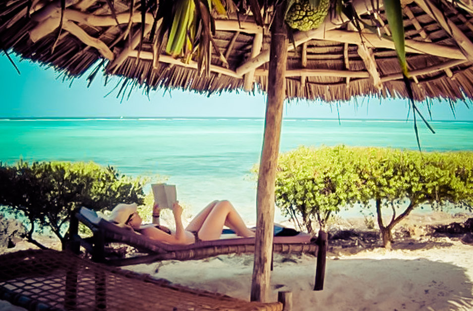 Picture of a woman reading and sunbathing on a beach in Tanzania