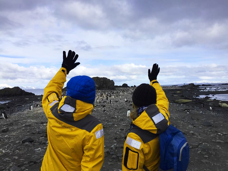 Two people waving at penguins on an island in Antarctica